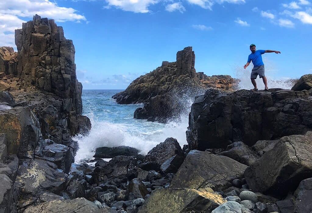 Trin dodging a wave on the basalt lava rocks along the coast of Kiama on the coastal walk