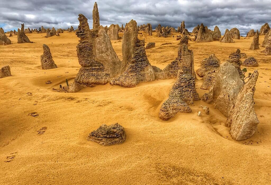 Pinnacles of sandstone stand in a desert of reddish sand