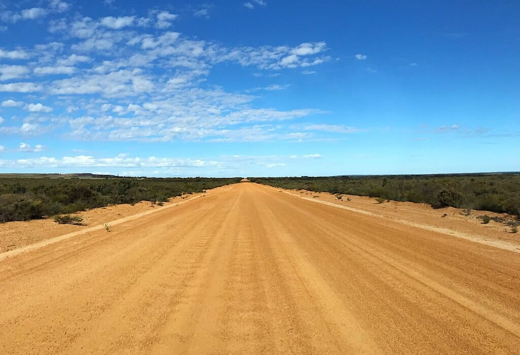 A flat dirt road with low scrub brush surrounding it. The horizon is flat in the distance with a blue sky above.