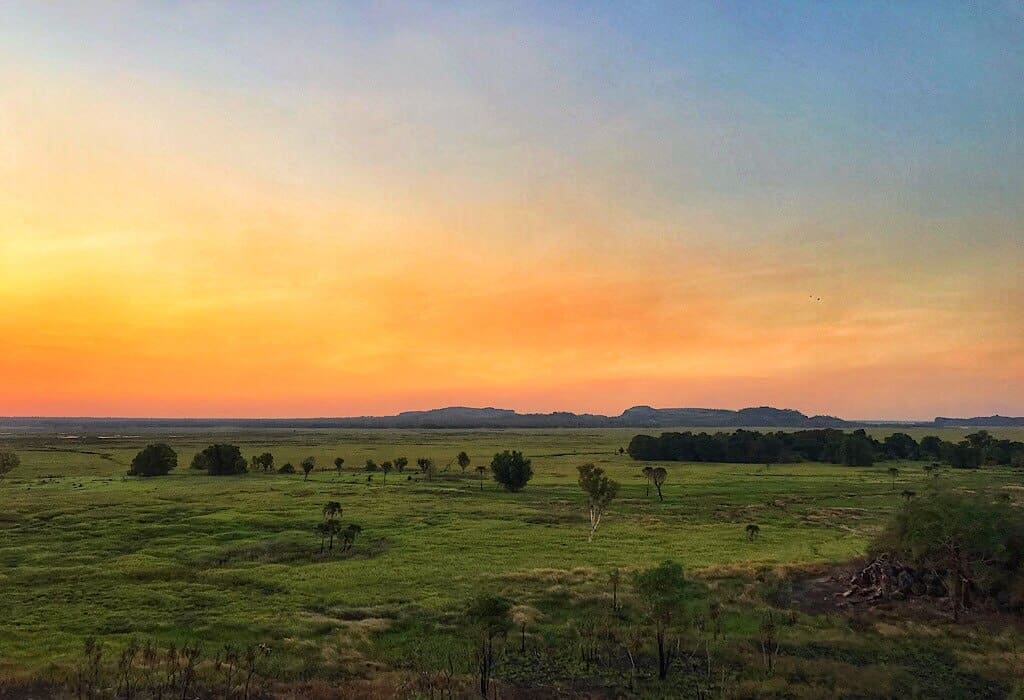 Sunset over a billabong with mountains in the distance