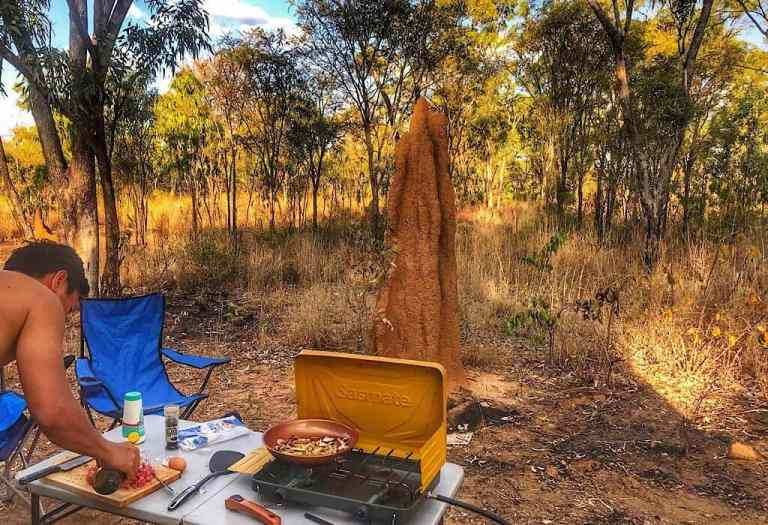 Dinner in the outback. Trin making burgers in the outback. A termite mound is in front of him