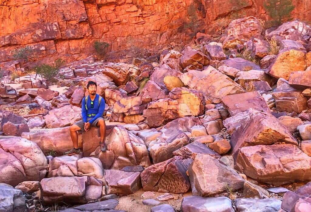Trin sitting on the boulders at the mouth of the Ormiston Gorge