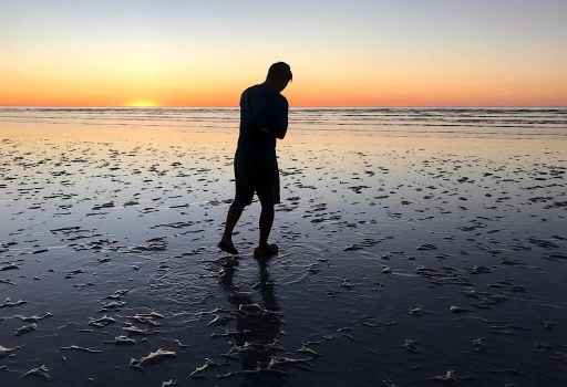 Trin standing on 80 mile beach at sunset in Western Australia