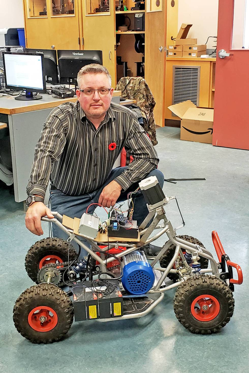 Lake City Secondary School robotics teacher Nick MacDonald poses with the rover his students are creating for their Capstone Project. (Photo submitted)