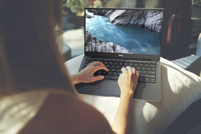 Photo of a woman working on a Dell XPS 13, from behind, with her hands on the keyboard