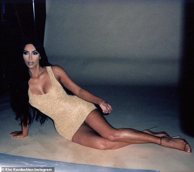 Kim Kardashian puts on a leggy display as she poses in a tiny gold mini dress (Photos)