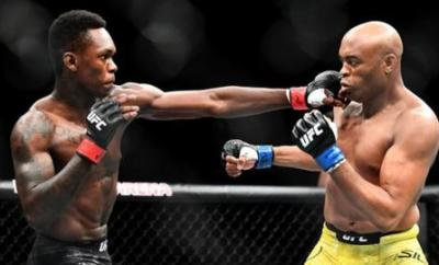 Israel Adesanya (left) aims a blow at Anderson Silva