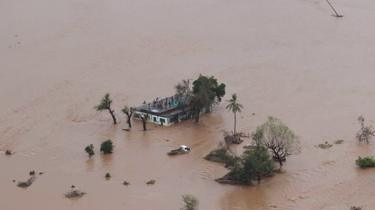 People stand on a roof of a house cut off by flood water