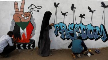 "Demonstrators in Khartoum paint a mural reading ""Freedom"", 14 April 2019"