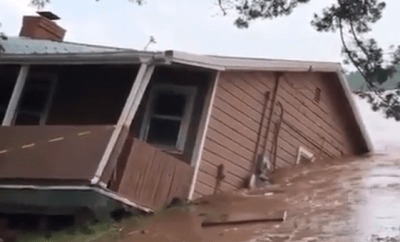 Watch as erosion caused by flooding sweeps home into river