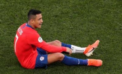 Alexis Sanchez sits on the ground after suffering an injury
