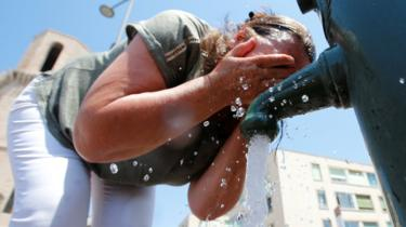 A woman cools off in a water fountain in Marseille as a heatwave hits France in June