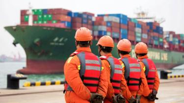 Workers wait to unload shipping containers on a port in Qingdao in China