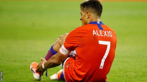 Alexis Sanchez on the ground after injuring his ankle playing for Chile against Colombia