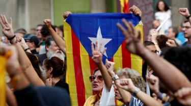 Supporters of Catalonia's independence hold an Estelada (Catalan separatist flag) as they gesture during a protest against the upcoming ruling of the Spanish Supreme Court, 13 October 2019