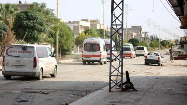 A convoy of ambulances and other vehicles leaves the north-eastern Syrian border town of Ras al-Ain on October 20, 2019