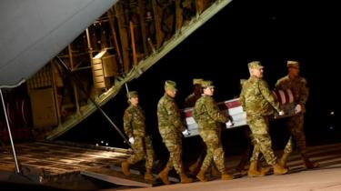 Military personnel carry a transfer case for fallen service member Navy Ensign Joshua Watson. 8 Dec 2019