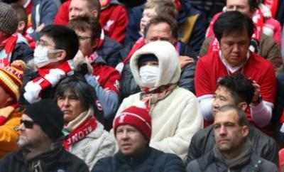 Fans uses masks at a Premier League game