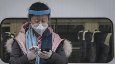 A masked traveller sends a message on her phone on the platform at Hankou Railway Station in Wuhan