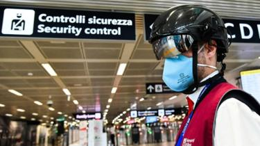 "Image shows a Fiumicino airport employee wearing a ""Smart-Helmet"" portable thermoscanner to screen passengers and staff for COVID-19"