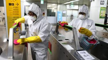 Disinfection professionals wearing protective gear spray anti-septic solution against the coronavirus (COVID-19) at a sybway station