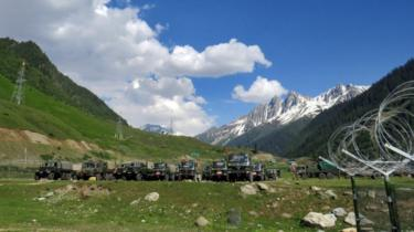 Indian army soldiers walk past their parked trucks at a makeshift transit camp before heading to Ladakh, near Baltal, southeast of Srinagar,16 June 2020