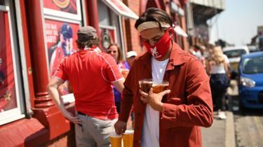 Fan carries beers outside Anfield pub