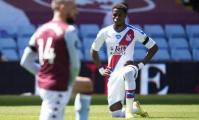 Wilfried Zaha kneeling before Crystal Palace's Premier League game at Aston Villa on Sunday
