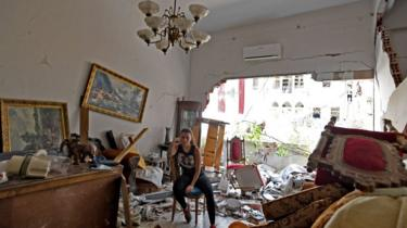 A woman sits amidst the rubble in her damaged house in the Lebanese capital Beirut on August 6, 2020, two days after a massive explosion shook the Lebanese capital.