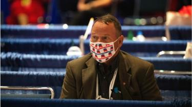 A delegate wears a mask with the Republican Party's elephant logo