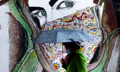 A woman wearing a face mask walks past a mural in Rome's Trastevere district