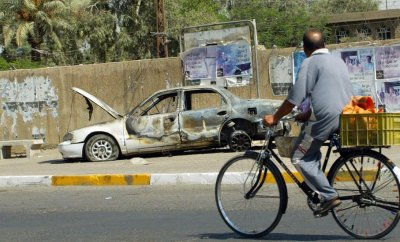 An Iraqi man rides a bicycle passing by a remains of a car burnt during a deadly incident involving Blackwater guards in Baghdad in September 2007