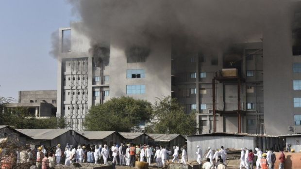 Workers stand outside the site of a deadly fire at the Serum Institute of India's facility in Pune