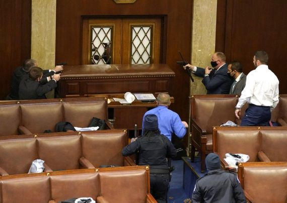 Capitol police officers point their guns at a door that was vandalized in the House Chamber during a joint session of Congress on 6 January 2021 in Washington, DC.