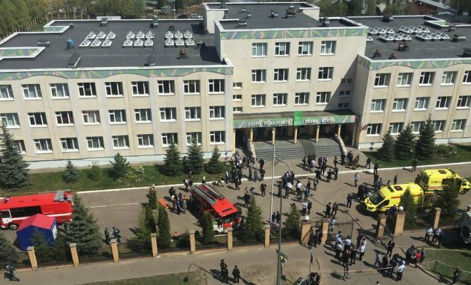 Ambulances and police cars gather outside a school in the aftermath of a shooting, in Kazan, Russia, 11 May 2011
