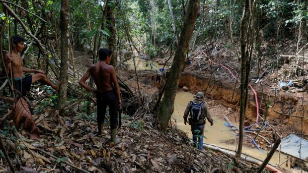 Yanomami Indians follow agents of Brazil's environmental agency in a gold mine during an operation against illegal gold mining on indigenous land on 17 April 2016