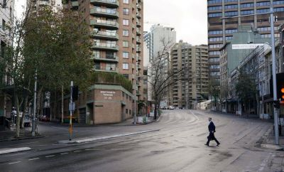 A man crosses a deserted street in central Sydney during lockdown