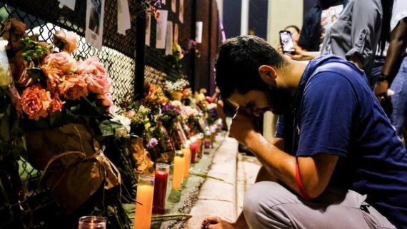 Leo Soto, 25, who lost his friend in the disaster, reacts as people hang up signs of missing residents