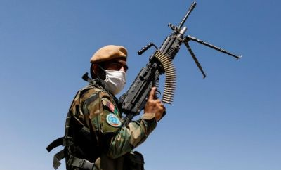 An Afghan National Army soldier holds a machine gun at a checkpoint on the outskirts of Kabul