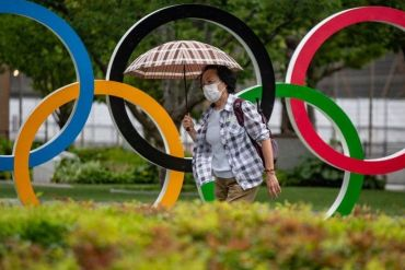 A woman holds an umbrella walking past the Olympic Rings in front of Japan Olympic Museum in Tokyo