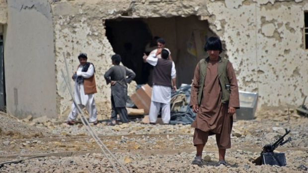 Afghan security forces guard a damaged building