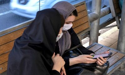 Two women look at a mobile phone at a bus stop in Tehran, Iran (30 May 2021)