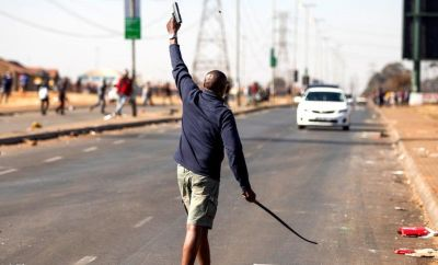 A man fires a hand gun in the air to disperse a mob of alleged looters outside of the Chris Hani Mall in Vosloorus, on July 14, 2021