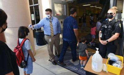 Students in a different Florida region, Orlando, have their temperatures checked
