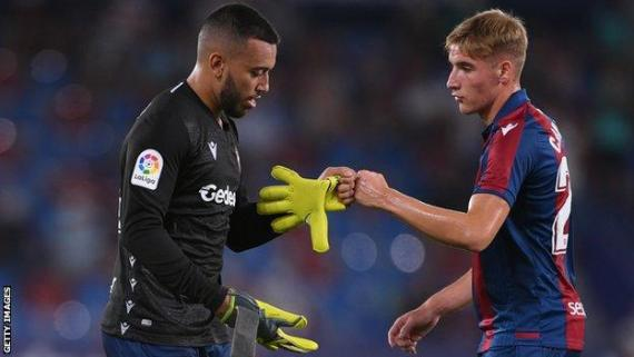 Red-carded Levante keeper Aitor Fernandez hands the gloves to defender Ruben Vezo