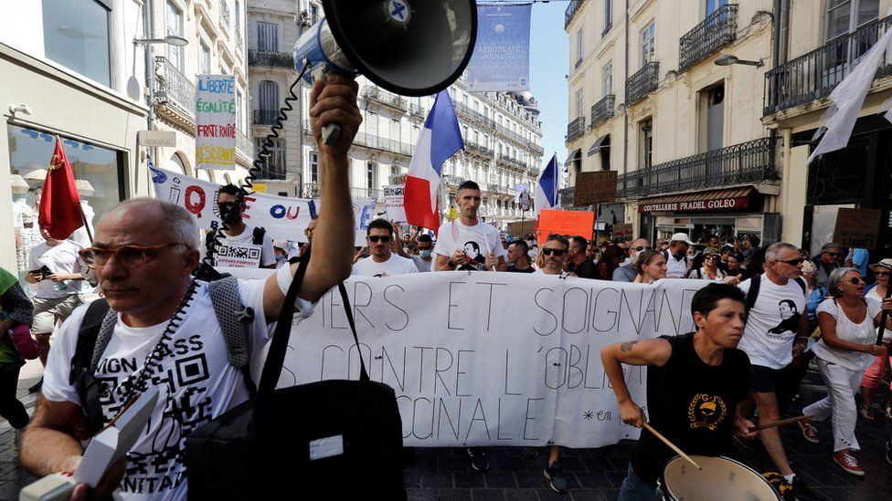 """Protesters holds a banner reading """"Firefighters and health workers against the vaccine obligation"""" during a demonstration against the COVID-19 sanitary pass"""
