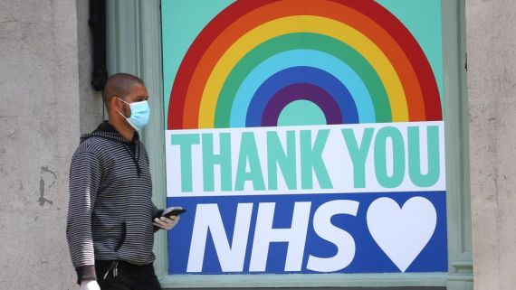A man walks past a thank you message to the NHS in central London on April 16, 2020