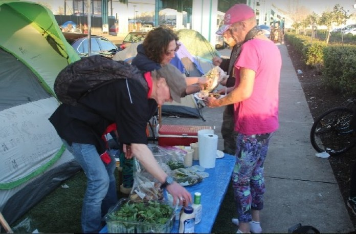 Homeless campers share a meal under the freeway in a community that's very different from what C.W. Nevius portrayed