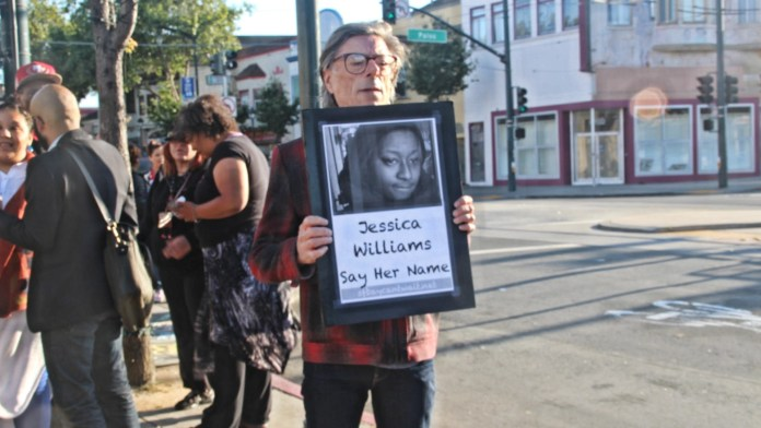 A protestor holds a photo of Jessica William, provided by her family. Photo by Sana Saleem