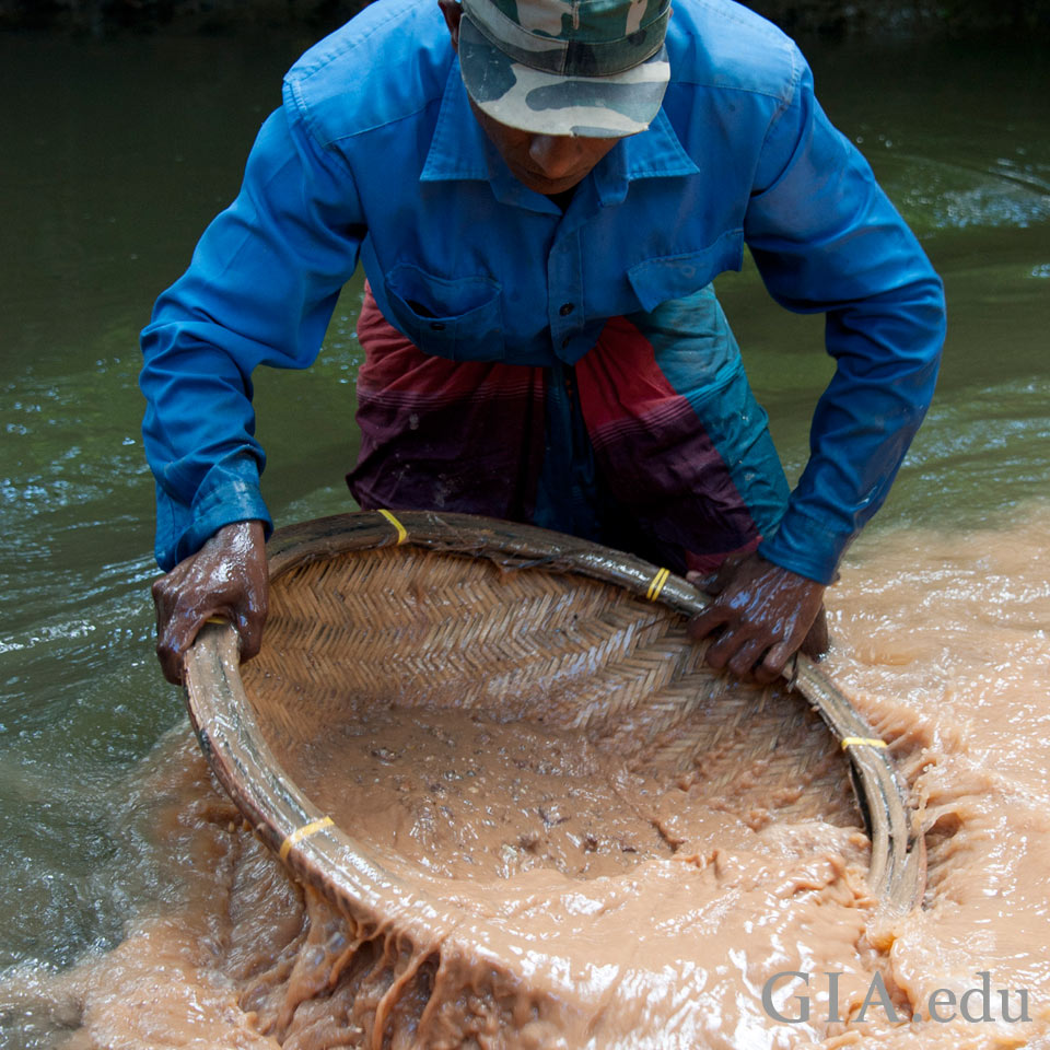Miner searching in river gravel